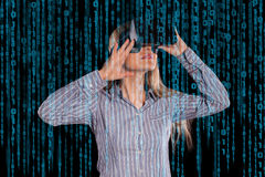 Intrigued woman in grey shirt wearing virtual reality 3D headset Royalty Free Stock Image