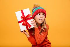 Intrigued Young girl in sweater and hat holding gift box stock photo