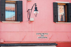 Intriguing Street name under a lamp by a house wall. On the Island of Burano in Italy Royalty Free Stock Photography
