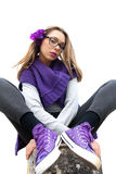Intriguing teen dressed in purple. Low angle view of a teenage girl sitting cross-legged with nerdy glasses and intriguing expression Stock Photos