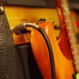 Introduca la presa inserita all'amplificatore combinato con la chitarra elettrica su fondo nero Immagini Stock Libere da Diritti
