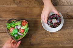 Introduce the alternative of eating between donuts and salads. stock photos