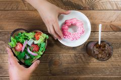 Introduce the alternative of eating between donuts and salads royalty free stock images