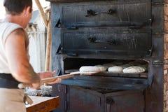 Introducing artisan baker dough in the oven Stock Photos