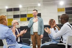 Introduction at Support Group Meeting. Portrait of smiling mature men    introducing himself during therapy session in support group to people clapping, copy stock image