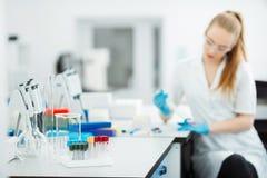 Introduisez à la pipette laisser tomber un échantillon dans un tube à essai Assistant de laboratoire analysant le sang dans le la photographie stock libre de droits