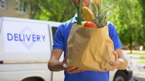 Introduza no mercado o trabalhador que dá o saco de mantimento, serviço de entrega dos bens, ordem expressa do alimento vídeos de arquivo