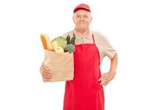 Introduza no mercado o vendedor que mantém um saco completo dos mantimentos Fotografia de Stock Royalty Free