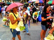 Introduza no mercado o vendedor que vende flores no quiapo nas Filipinas imagem de stock