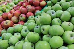 Introduza no mercado prateleiras com verde e as maçãs maduras vermelhas fecham-se acima Fotografia de Stock