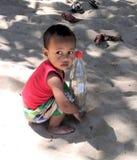 Intrometido seja, Madagáscar - 09/21/2018: Uma criança africana com um olhar melancólico que guarda uma garrafa do casco em suas  fotografia de stock royalty free