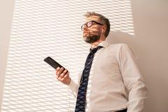 Introspectieve zakenman die aan muziek op telefoon luisteren royalty-vrije stock afbeeldingen