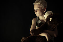 Introvert little boy in dim light holding toy Stock Images