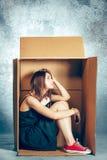 Introvertiertekonzept Frau, die innerhalb des Kastens sitzt und mit Telefon arbeitet stockfoto