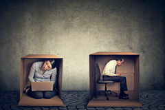 Introverts. Man and woman sitting inside boxes working on laptop Royalty Free Stock Images