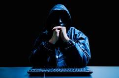 Intru anonyme dans le masque et le hoodie blancs Visage foncé obscurci avec l'ordinateur de clavier dans l'obscurité Voleur de do photos stock