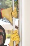 Ladrón que se rompe a través de la ventana del hogar fotografía de archivo