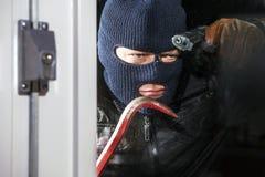 Intruz z wrona barem i ręka pistoletem zdjęcie stock