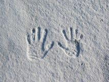 Intryck av mänskliga händer i den kalla vita snön arkivfoto
