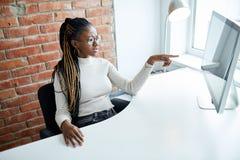 Intrygująca afro dziewczyna wskazująca przy komputerem gdy niektóre problemy z nim zdjęcie stock