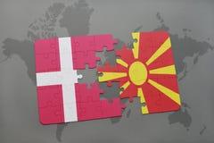 intryguje z flaga państowowa Denmark i Macedonia na światowej mapy tle Zdjęcia Stock