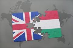 intryguje z flaga państowowa wielki Britain i Hungary na światowej mapy tle Obrazy Stock