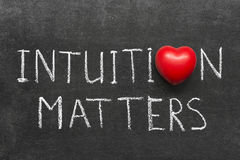 Intuition matters. Phrase handwritten on blackboard with heart symbol instead of O Stock Photos