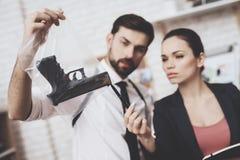 Intymna detektywistyczna agencja Mężczyzna i kobieta jesteśmy przyglądającym armatnim wskazówką i brać notatki obrazy stock