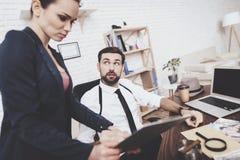 Intymna detektywistyczna agencja Mężczyzna i kobieta jesteśmy przyglądającym pastylką w biurze obrazy royalty free