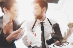 Intymna detektywistyczna agencja Mężczyzna i kobieta jesteśmy przyglądającym pistoletem z powiększać - szkło fotografia royalty free