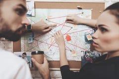 Intymna detektywistyczna agencja Mężczyzna i kobieta jesteśmy przyglądającym wskazówki mapą, pije kawę zdjęcia royalty free