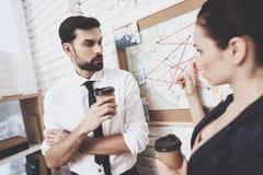 Intymna detektywistyczna agencja Mężczyzna i kobieta jesteśmy przyglądającym wskazówki mapą, pije kawę fotografia royalty free