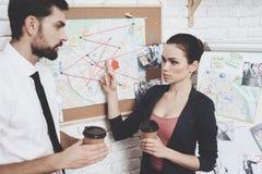 Intymna detektywistyczna agencja Mężczyzna i kobieta jesteśmy przyglądającym wskazówki mapą, pije kawę obrazy royalty free