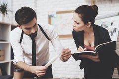 Intymna detektywistyczna agencja Mężczyzna jest przyglądającym wskazówką, kobieta bierze notatki w notatniku obraz royalty free