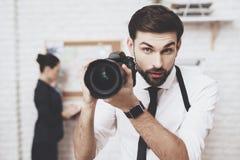 Intymna detektywistyczna agencja Mężczyzna pozuje z kamerą, kobieta jest przyglądającym wskazówki mapą zdjęcie royalty free
