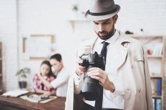 Intymna detektywistyczna agencja Mężczyzna pozuje z kamerą, kobieta trzyma jej córki zdjęcia royalty free
