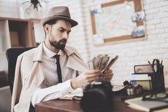 Intymna detektywistyczna agencja Mężczyzna siedzi przy stołowym odliczającym pieniądze fotografia stock