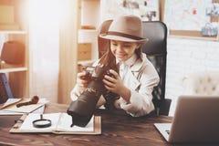 Intymna detektywistyczna agencja Mała dziewczynka patrzeje fotografie w kamerze siedzi przy biurkiem obrazy stock