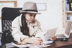 Intymna detektywistyczna agencja Mała dziewczynka patrzeje różne fotografie siedzi przy biurkiem obrazy royalty free