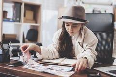 Intymna detektywistyczna agencja Mała dziewczynka patrzeje różne fotografie siedzi przy biurkiem zdjęcia royalty free
