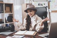 Intymna detektywistyczna agencja Mała dziewczynka rozprzestrzenia out ona siedzi przy biurkiem ręki obraz stock