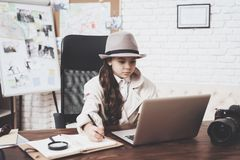 Intymna detektywistyczna agencja Mała dziewczynka siedzi przy biurkiem bierze notatki blisko laptopu zdjęcie royalty free