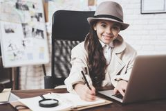 Intymna detektywistyczna agencja Mała dziewczynka siedzi przy biurkiem bierze notatki blisko laptopu obrazy royalty free