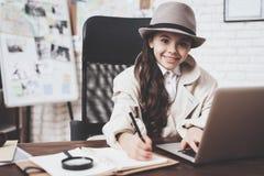 Intymna detektywistyczna agencja Mała dziewczynka siedzi przy biurkiem bierze notatki blisko laptopu zdjęcie stock