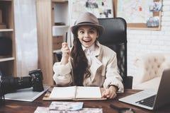 Intymna detektywistyczna agencja Mała dziewczynka siedzi przy biurkiem bierze notatki w notatniku obrazy royalty free