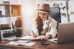Intymna detektywistyczna agencja Mała dziewczynka siedzi przy biurkiem bierze notatki w notatniku obraz stock