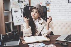 Intymna detektywistyczna agencja Mała dziewczynka siedzi przy biurkiem bierze notatki w notatniku Obrazy Stock