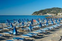 Intymna plaża wyposażająca z błękitnymi deckchairs i plażowymi parasolami fotografia royalty free