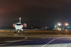 Intymny dżetowy samolot parkujący w lotnisku przy nocą biznesu zegarów pojęcia różna pokazywać czas timezone podróż Zdjęcie Stock