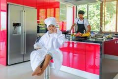Intymny Tajlandzki szefa kuchni kucharstwo, jego mały syn w szefa kuchni ` s kapeluszowy niedaleki s Zdjęcie Stock